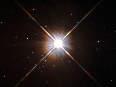 "Shining brightly in this Hubble image is our closest stellar neighbour: Proxima Centauri. Proxima Centauri lies in the constellation of Centaurus (The Centaur), just over four light-years from Earth. Although it looks bright through the eye of Hubble, as you might expect from the nearest star to the Solar System, Proxima Centauri is not visible to the naked eye. Its average luminosity is very low, and it is quite small compared to other stars, at only about an eighth of the mass of the Sun. However, on occasion, its brightness increases. Proxima is what is known as a ""flare star"", meaning that convection processes within the star's body make it prone to random and dramatic changes in brightness. The convection processes not only trigger brilliant bursts of starlight but, combined with other factors, mean that Proxima Centauri is in for a very long life. Astronomers predict that this star will remain middle-aged — or a ""main sequence"" star in astronomical terms — for another four trillion years, some 300 times the age of the current Universe. These observations were taken using Hubble's Wide Field and Planetary Camera 2 (WFPC2). Proxima Centauri is actually part of a triple star system — its two companions, Alpha Centauri A and B, lie out of frame. Although by cosmic standards it is a close neighbour, Proxima Centauri remains a point-like object even using Hubble's eagle-eyed vision, hinting at the vast scale of the Universe around us."